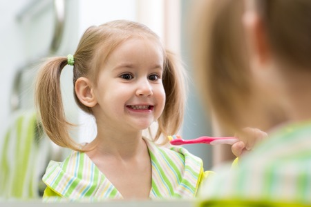Cute child girl brushing teeth and looking in mirror in bathroom