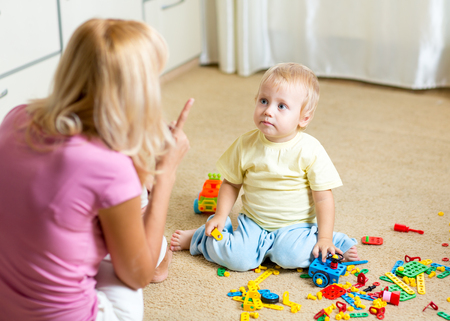 Mother scolding her little kid son for disorder at home