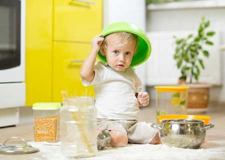 Child toddler boy sitting on the kitchen floor and playing with flour.