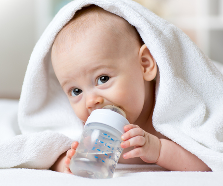 wash: Happy baby drinks water from bottle wrapped towel after bathing