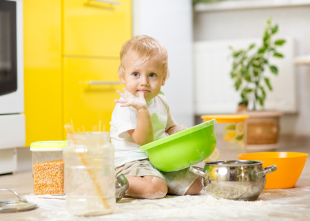Kid toddler boy sitting on the kitchen floor and playing with flour. Reklamní fotografie