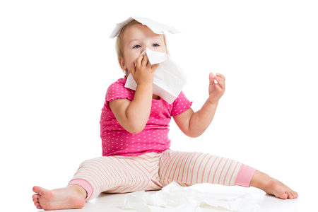Little child blows nose while sitting on floor, isolated over white