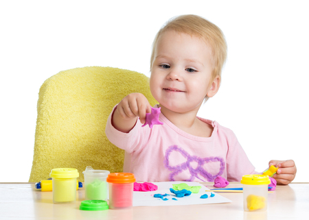 Little girl learning to use colorful play dough isolated on white background Stock Photo