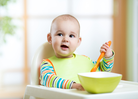 Happy cute infant baby boy spoon eats itself Banque d'images
