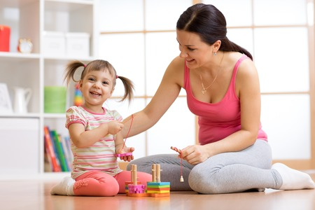 Cute woman and kid girl playing educational toys at home
