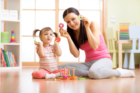 Happy mother and her child playing with colorful logical sorter toy Banque d'images