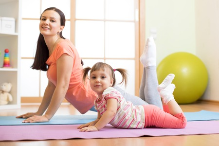 Mother and child daughter doing yoga exercises on floor in room at home. Family having fun indoors with fitness.