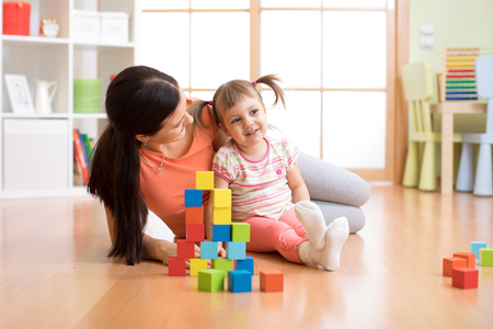 Cute mother and child girl play with cubes together Banque d'images