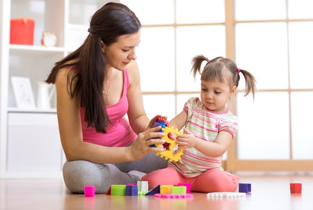 mother and her child playing with colorful logical sorter toy Banque d'images
