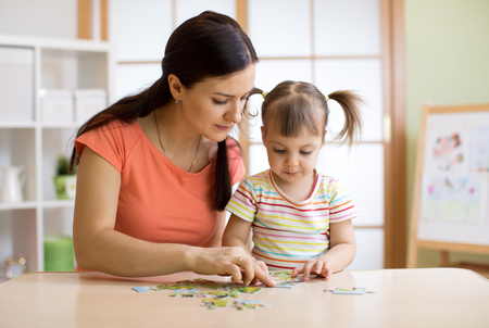 Mother and daughter playing at home. They assembling Jigsaw Puzzle. Standard-Bild