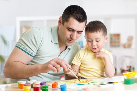 Father and little boy of three years having fun painting at home Stock Photo