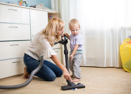 Cleaning up the room together - mother and her kid son with vacuum cleaner Banque d'images