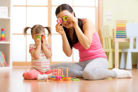 Kid girl and her mother have a fun playing together with puzzle toys. Woman and child toddler sitting on floor and laughing.