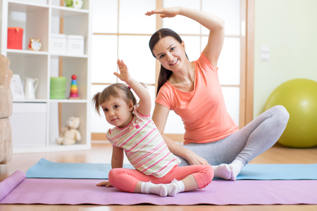 Active mom and child daughter are engaged in fitness, yoga, exercise at home Banque d'images
