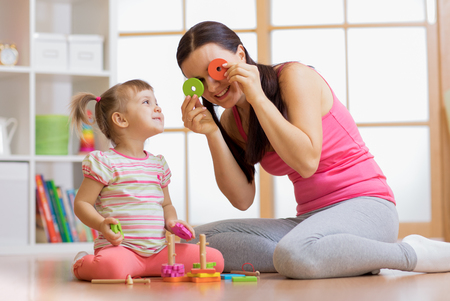 Child girl and mother have a fun playing together with puzzle toys Stockfoto