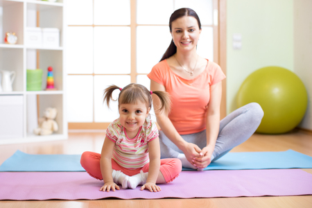 Mother and child daughter practicing yoga together in living room at home. Sport and family concept. Banque d'images