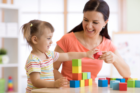 Cute woman and child girl playing educational toys at kindergarten or nursery room