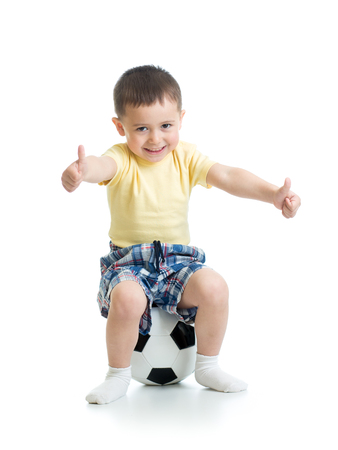 Child boy is sitting on soccer ball with thumbs up sign.