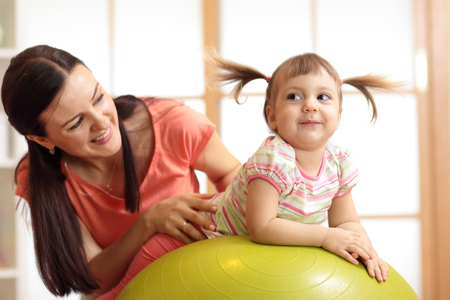 Mother and child daughter playing with gymnastic ball at home Banque d'images