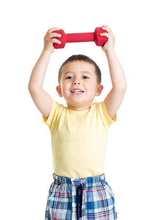 Child toddler is engaged in physical training with red dumbbell