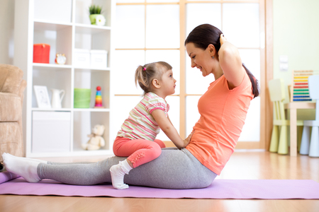 Mother and her child daughter are engaged in fitness, yoga, exercise at home. Kid and woman swing press on stomach.