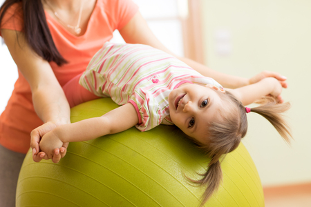 Cute kid girl stretching on pilates fitness ball with mom in gym Banque d'images