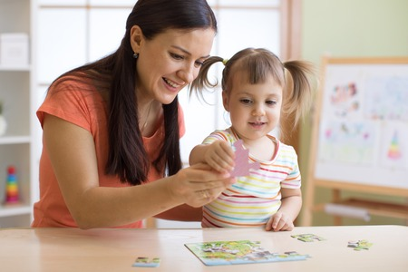mother and daughter doing playing puzzle toy together on the table in children room