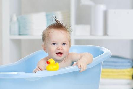 adorable baby having bath in blue tub