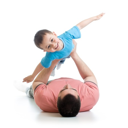 happy father playing with son kid lying on floor