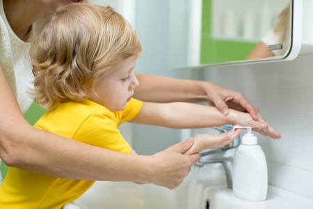 Mother and kid son washing their hands in the bathroom. Care and concern for children. Banco de Imagens