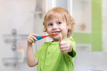 Little boy brushing his teeth in the bathroom. Smiling child holding toothbrush and showing thumbs up. Standard-Bild