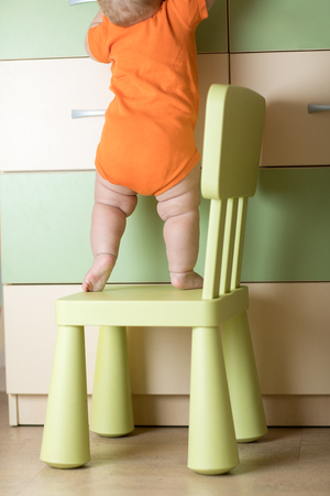Baby climbing on chair. Kids safety conception. Stock Photo