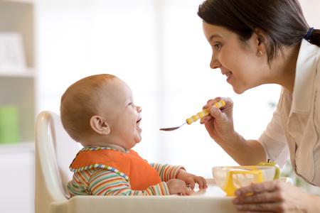 Mother spoon-feeding her child boy 스톡 콘텐츠