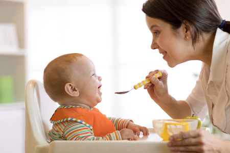 Mother spoon-feeding her child boy Stock Photo