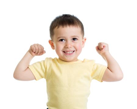 Porträt des netten Kindes die Muskeln seiner Arme zeigend, lokalisiert auf Weiß