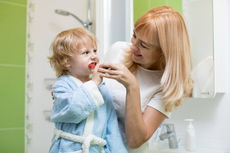 Mother teaching and helping kid son how to brush his teeth