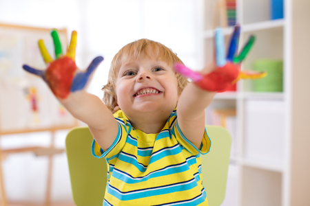 cute cheerful kid boy showing hands painted in bright colors Stock Photo