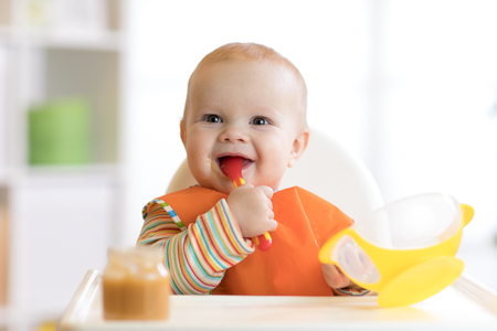 Happy infant baby boy spoon eats itself