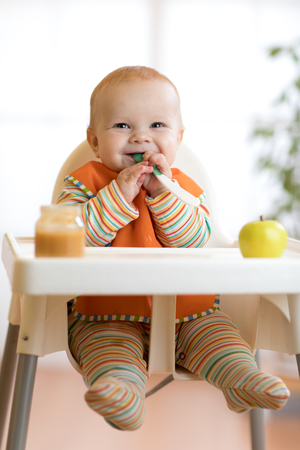 Cheerful baby child eats food itself with spoon. Portrait of happy kid boy in high-chair. Stock Photo