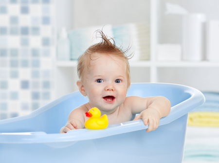 cute baby having bath in blue tub
