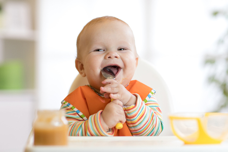 Cheerful baby child eats food itself with spoon. Portrait of happy kid boy in high-chair. Foto de archivo