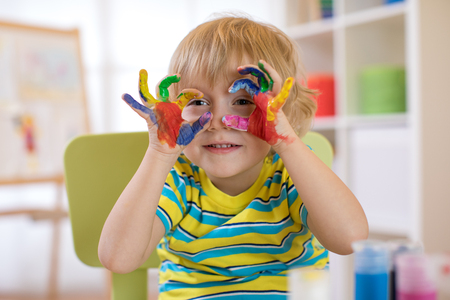 cute cheerful kid with hands painted in bright colors Stock Photo