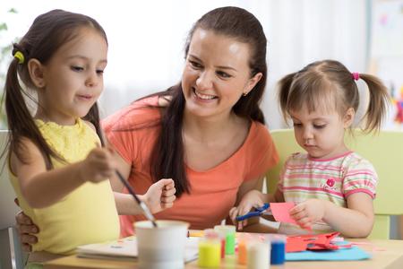 kinderenmeisjes en moederhanden die bij kinderdagverblijf thuis maken Stockfoto