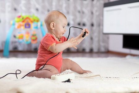 8 months old age baby pulling cables from electrical extension