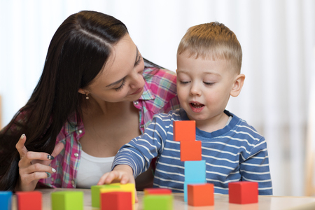 Child boy together with mother playing toys