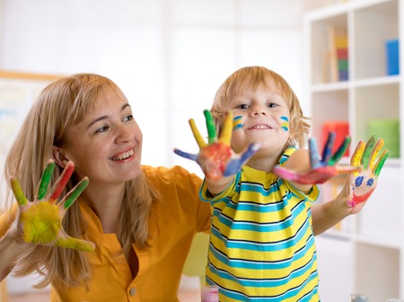 Child boy and his mother with painted hands. Kid drawing and coloring with teacher in daycare center or playschool. Stock Photo