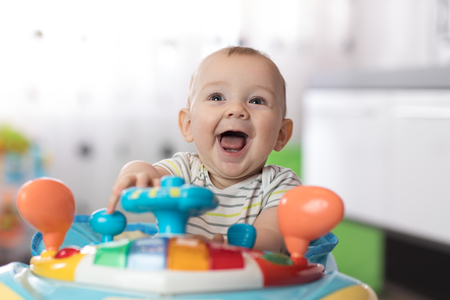 Portrait of baby toddler in baby walker. Expressive child plays toys. Banque d'images