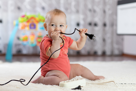8 months age baby curious looking with electronic plug Stock fotó