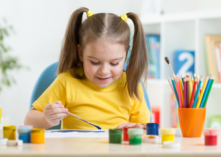 Child girl painting picture on home interior background