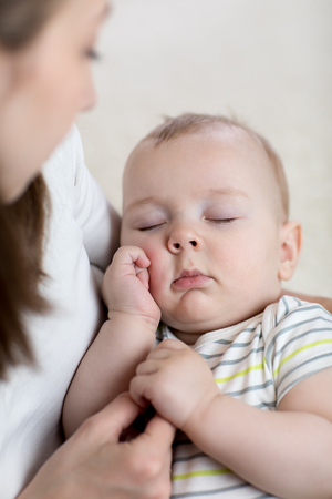 Mother lulling her baby son at home
